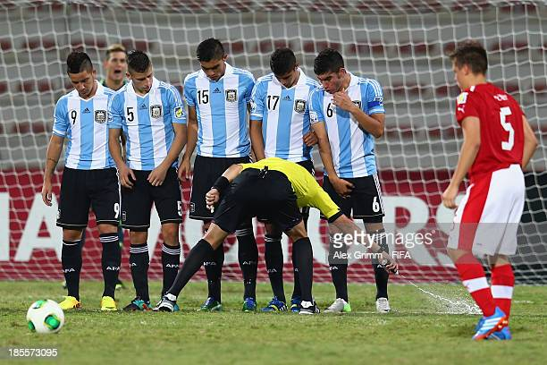 Referee Jair Marrufo marks out the position for the wall at a freekick with a spray during the FIFA U17 World Cup UAE 2013 Group E match between...