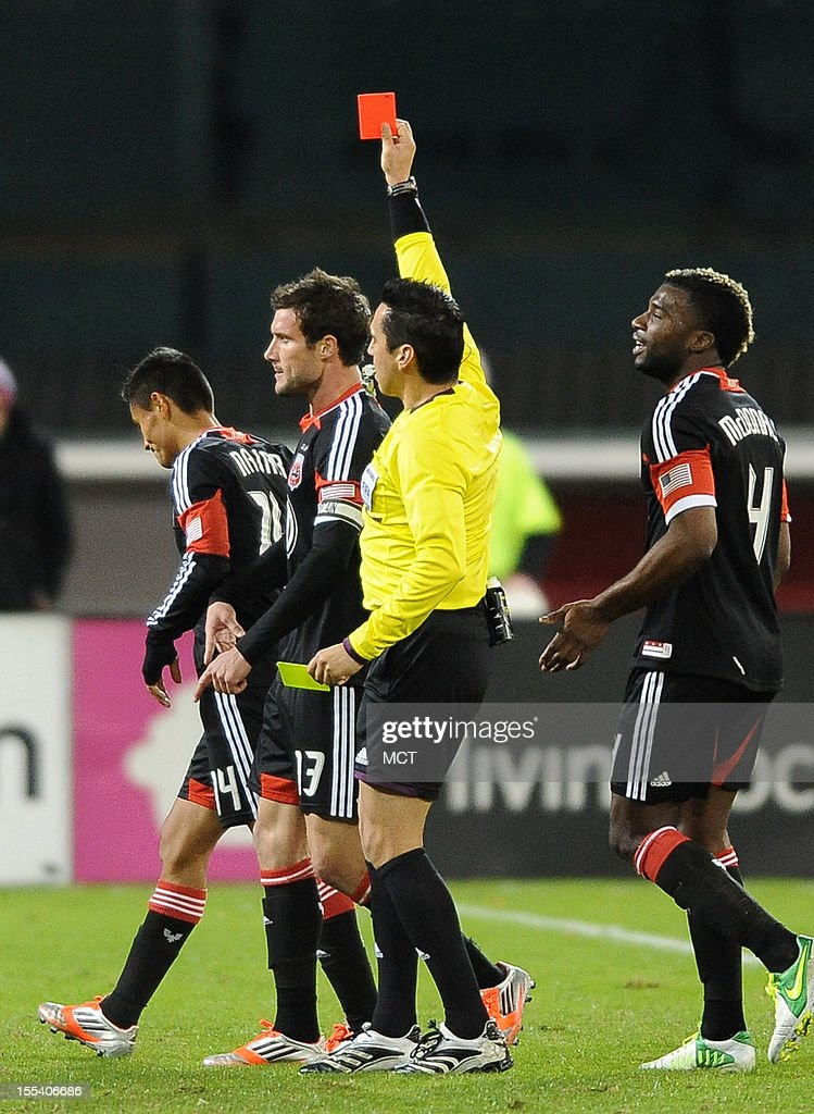 Referee Jair Marruto issues a red card and a game ejection for an insult to D.C. United midfielder Andy Najar (14), left, during second-half action between United and the New York Red Bulls in an MLS Eastern Conference semifinal at RFK Stadium in Washington, D.C., Saturday, November 3, 2012. United and the Red Bulls tied 1-10.