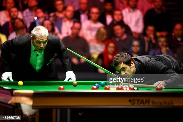 Referee Jan Verhaas looks on as Ronnie O'Sullivan of Great Britain lines up a shot during his semifinal match against Neil Robertson of Australia on...