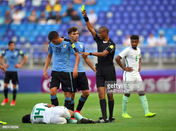 Referee Janny Sikazwe shows a yellow card to Uruguay's Rodrigo Bentancur as Saudi Arabia's Ali Alasmari lies on the pitch during their U20 World Cup...