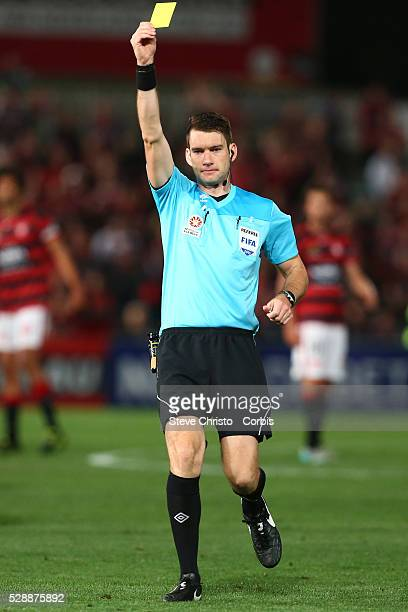Referee Jarred Gillett gives a yellow card during the round one ALeague match between the Western Sydney Wanderers and the Brisbane Roar at...