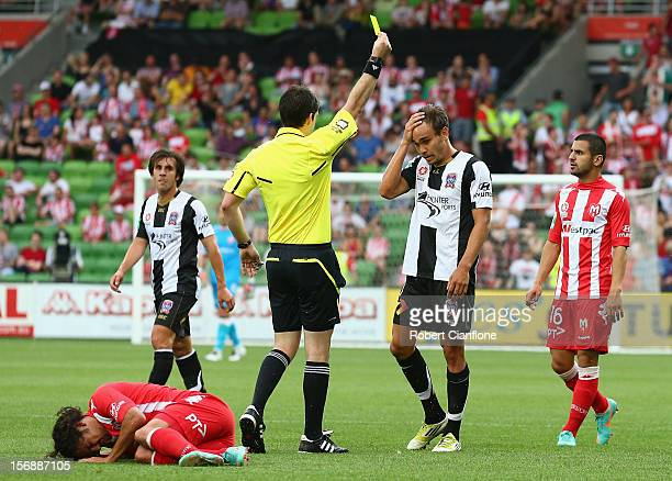 Referee Jarred Gillett gives a yellow card to James Brown of the Jets during the round eight ALeague match between the Melbourne Heart and the...
