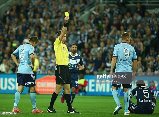 Referee Jarred Gillett gives a yellow card to Shane Smeltz of Sydney FC during the 2015 ALeague Grand Final match between the Melbourne Victory and...