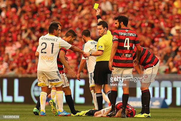 Referee Jarred Gillett gives Manny Muscat of the Phoenix a yellow card after a heavy clash with Aaron Mooy of the Wanderers who lies injured on the...