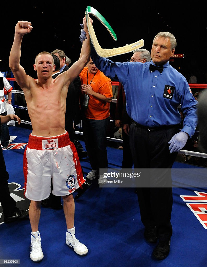 Referee Jay Nady (R) holds up Jason Litzau's hand as he celebrates his win over Rocky Juarez in their super featherweight bout at the Mandalay Bay Events Center April 3, 2010 in Las Vegas, Nevada. Litzau won by technical unanimous decision after the fight was stopped in the seventh round due to an earlier unintentional head-butt.