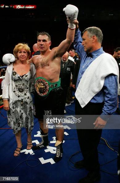Referee Jay Nady holds up the hand of Oleg Maskaev as he celebrates his 12th round TKO of Hasim Rahman with his wife Svetlana following their WBC...