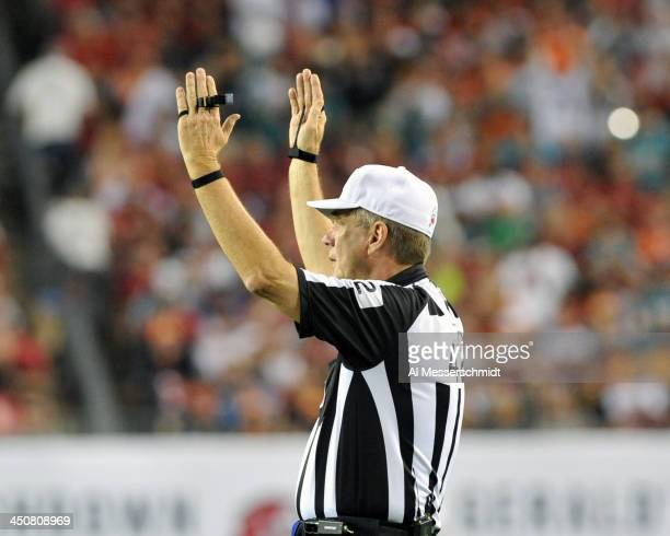 NFL referee Jeff Triplette signals a touchdown as the Miami Dolphins play against the Tampa Bay Buccaneers November 11 2013 at Raymond James Stadium...