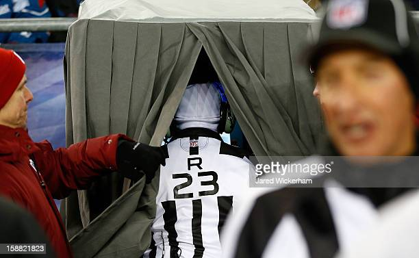Referee Jerome Boger looks at the screen in the instant replay booth during the game between the Miami Dolphins and the New England Patriots at...