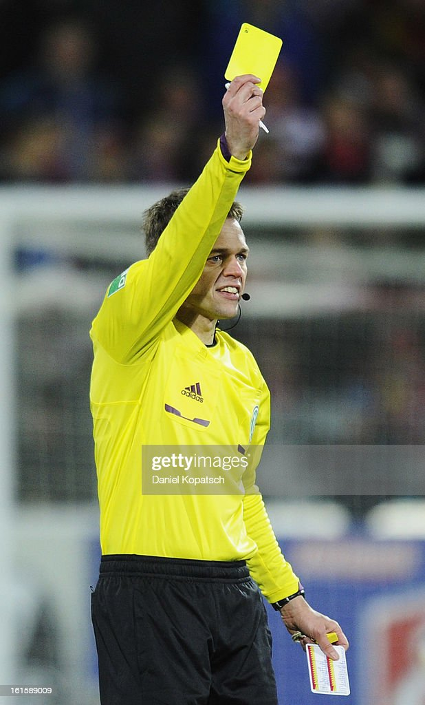 Referee Jochen Drees shows a yellow card during the Bundesliga match between SC Freiburg and Fortuna Duesseldorf 1895 at MAGE SOLAR Stadium on February 10, 2013 in Freiburg im Breisgau, Germany.