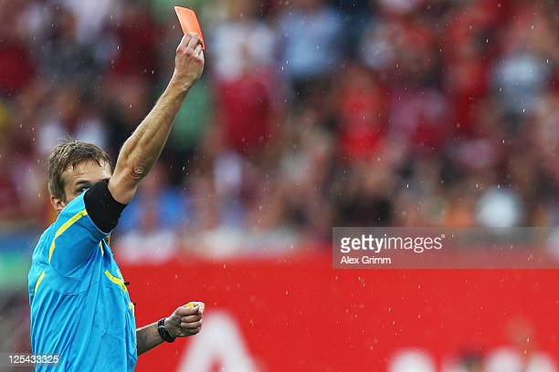Referee Jochen Drees shows the red card to goalkeeper Tim Wiese of Bremen during the Bundesliga match between 1 FC Nuernberg and Werder Bremen at...