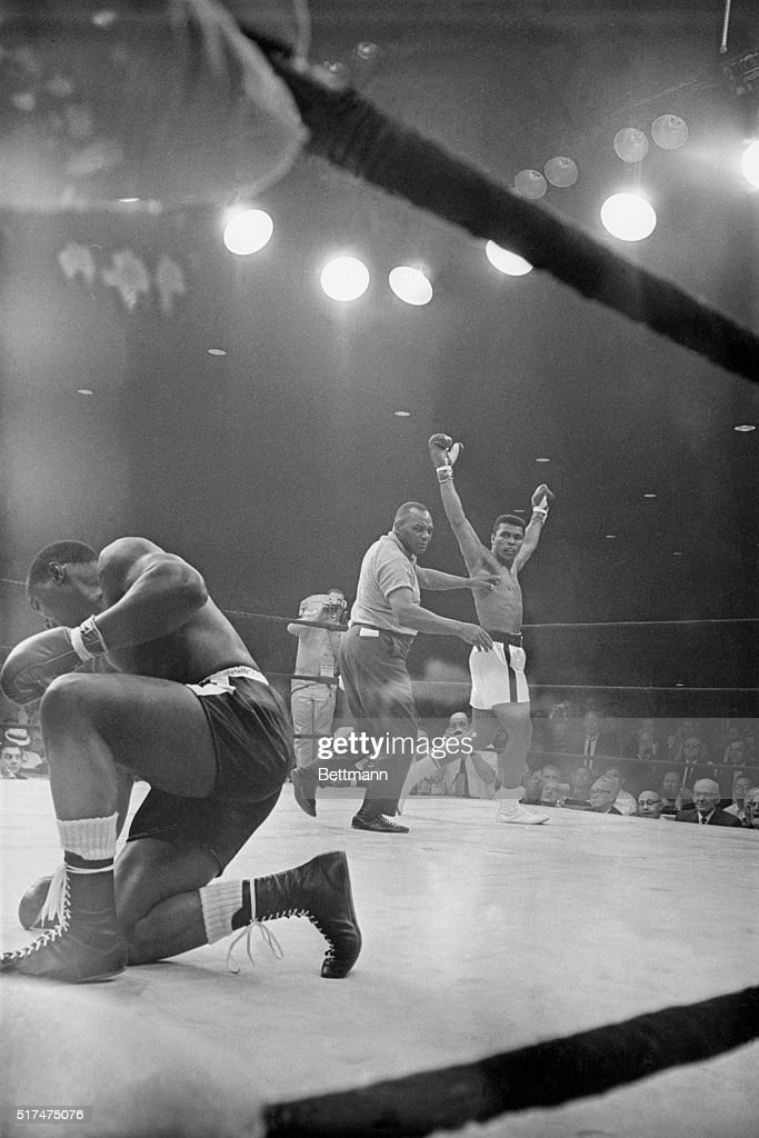 Referee Joe Wolcott guides heavyweight champion Muhammad Ali to a neutral corner after Ali downed challenger Sonny Liston in the first round of their championship fight on May 25th, 1965. Clay retained his crown by scoring a one-minute knockout victory over Liston in the controversial fight.