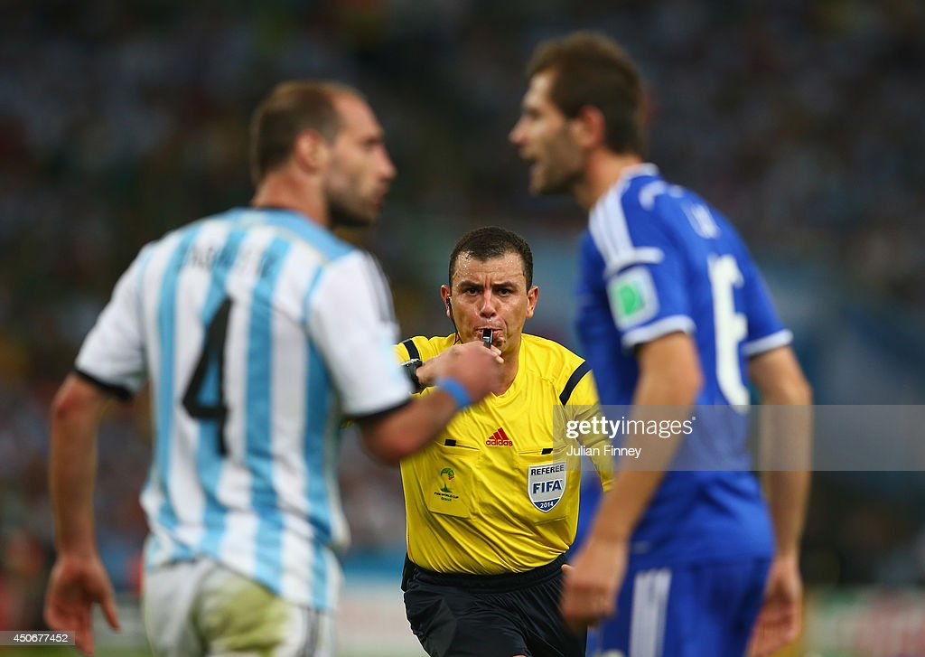 Referee <a gi-track='captionPersonalityLinkClicked' href=/galleries/search?phrase=Joel+Aguilar&family=editorial&specificpeople=4379873 ng-click='$event.stopPropagation()'>Joel Aguilar</a> reacts as Pablo Zabaleta of Argentina (L) and Senad Lulic of Bosnia and Herzegovina clash during the 2014 FIFA World Cup Brazil Group F match between Argentina and Bosnia-Herzegovina at Maracana on June 15, 2014 in Rio de Janeiro, Brazil.