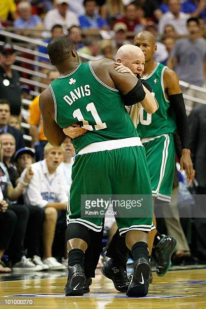 Referee Joey Crawford holds up Glen Davis of the Boston Celtics due to Davis being disoriented after he took an elbow to the head from Dwight Howard...