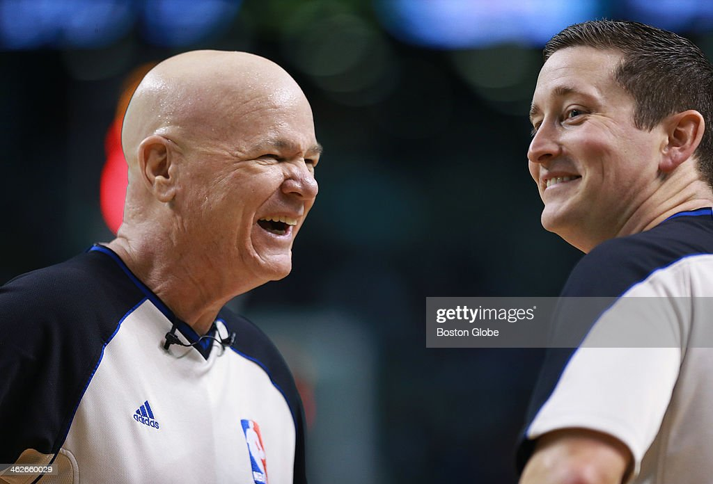 Referee Joey Crawford, left, pointed out something in the stands during a timeout to fellow referee Nick Buchert, right, which caused both men to break out in laughter. The Boston Celtics hosted the Houston Rockets in a regular season NBA game at TD Garden.