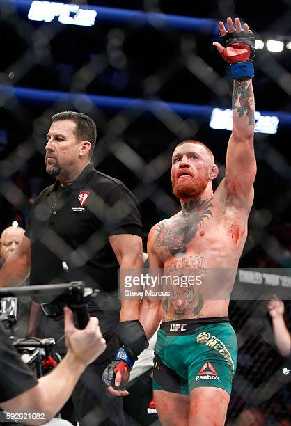 Referee John McCarthy stands next to Conor McGregor as he celebrates his majoritydecision victory over Nate Diaz in their welterweight rematch at the...