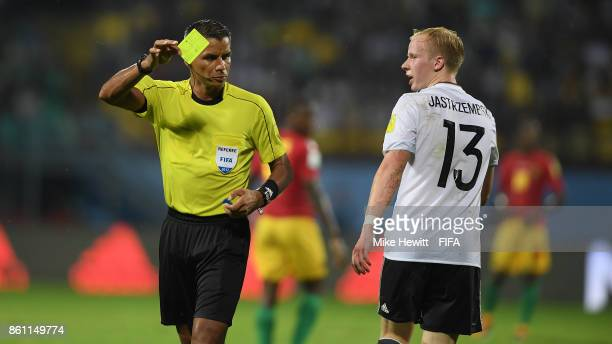 Referee John Pitti of Panama shows the yellow card to Dennis Jastrzembski of Germany during the FIFA U17 World Cup India 2017 group C match between...