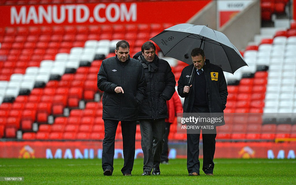 "Referee Jon Moss (R) and fourth official Phil Dowd (L) inspect the pitch before the English Premier League football match between Manchester United and West Bromwich Albion at Old Trafford in Manchester, north-west England on December 29, 2012. AFP PHOTO/ANDREW YATES USE. No use with unauthorized audio, video, data, fixture lists, club/league logos or ""live"" services. Online in-match use limited to 45 images, no video emulation. No use in betting, games or single club/league/player publications"