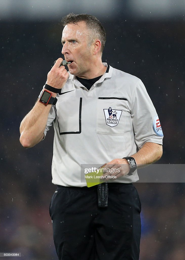 Referee Jon Moss blows his whistle and issues a yellow card during the Barclays Premier League match between Everton and Leicester City at Goodison Park on December 19, 2015 in Liverpool, England.