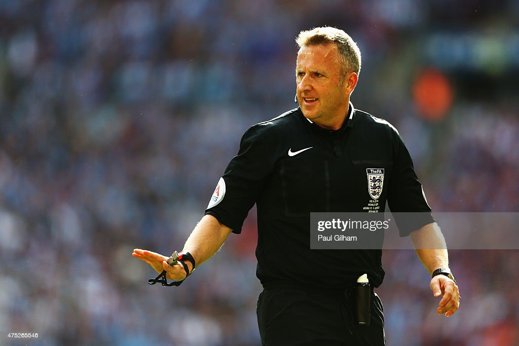 Referee Jon Moss signals during the FA Cup Final between Aston Villa and Arsenal at Wembley Stadium on May 30, 2015 in London, England.