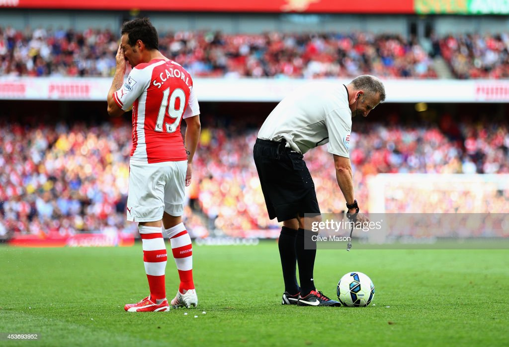 Referee Jon Moss struggles with the vanishing spray and <a gi-track='captionPersonalityLinkClicked' href=/galleries/search?phrase=Santi+Cazorla&family=editorial&specificpeople=709830 ng-click='$event.stopPropagation()'>Santi Cazorla</a> of Arsenal gets a face full during the Barclays Premier League match between Arsenal and Crystal Palace at Emirates Stadium on August 16, 2014 in London, England.