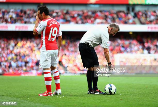 Referee Jon Moss struggles with the vanishing spray and Santi Cazorla of Arsenal gets a face full during the Barclays Premier League match between...