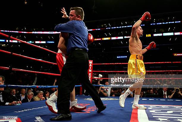 Referee Jon Schorle grabs Jesse Feliciano and stops the fight in the 10th round as Kermit Cintron celebrates winning the IBF Welterweight title fight...