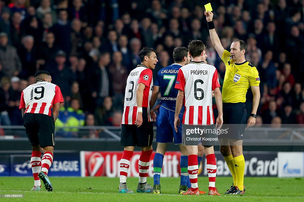 Referee <a gi-track='captionPersonalityLinkClicked' href=/galleries/search?phrase=Jonas+Eriksson+-+Referee&family=editorial&specificpeople=12731953 ng-click='$event.stopPropagation()'>Jonas Eriksson</a> of Sweden shows Daniel Caliguri of Wolfsburg (C) the yellow card during the UEFA Champions League Group B match between PSV Eindhoven and VfL Wolfsburg at Philips Stadion on November 3, 2015 in Eindhoven, Netherlands.