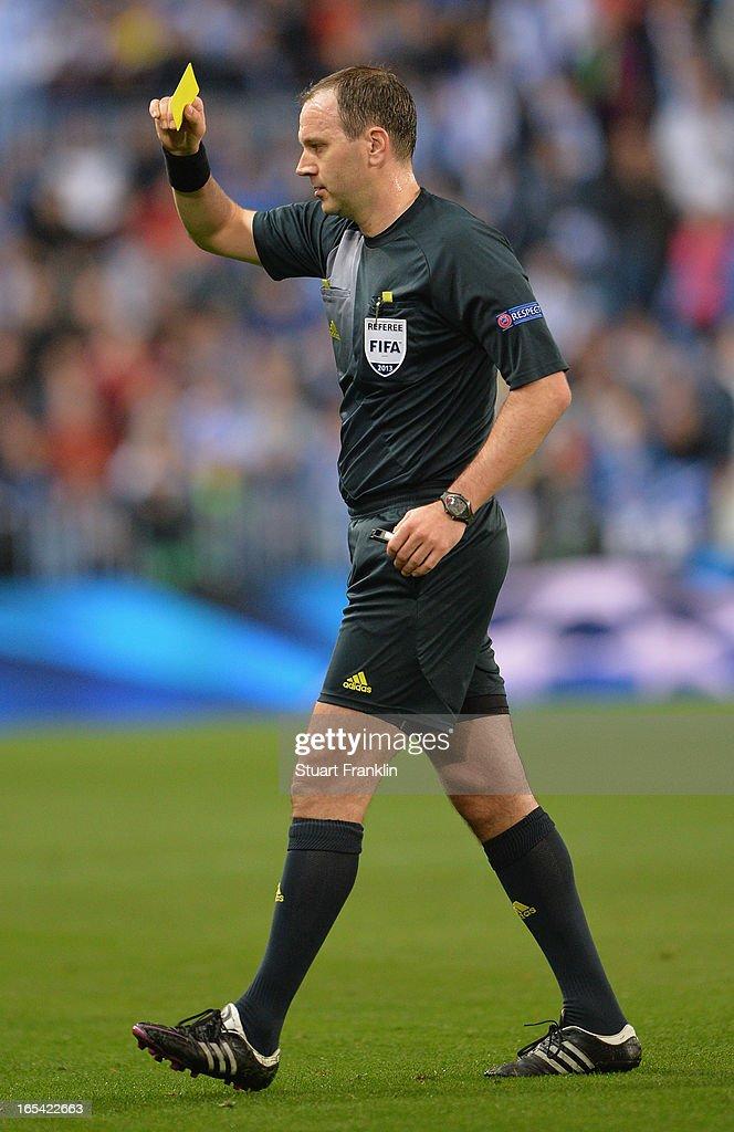 Referee Jonas Eriksson shows a yellow card during the UEFA Champion League quarter final first leg match between Malaga CF and Borussia Dortmund at La Rosaleda Stadium on April 3, 2013 in Malaga, Spain.