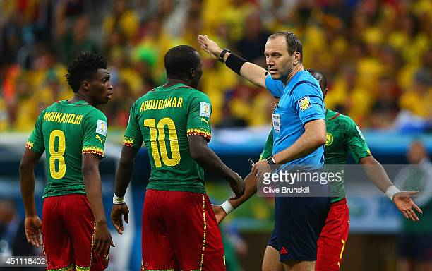 Referee Jonas Eriksson speaks to Benjamin Moukandjo and Vincent Aboubakar of Cameroon during the 2014 FIFA World Cup Brazil Group A match between...