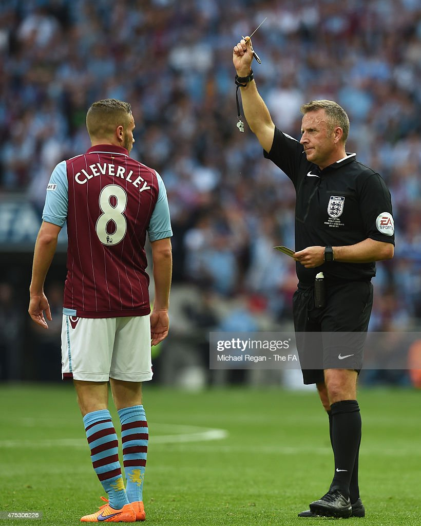 Referee Jonathan Moss awards a yellow card to Tom Cleverley of Aston Villa during the FA Cup Final between Aston Villa and Arsenal at Wembley Stadium on May 30, 2015 in London, England.