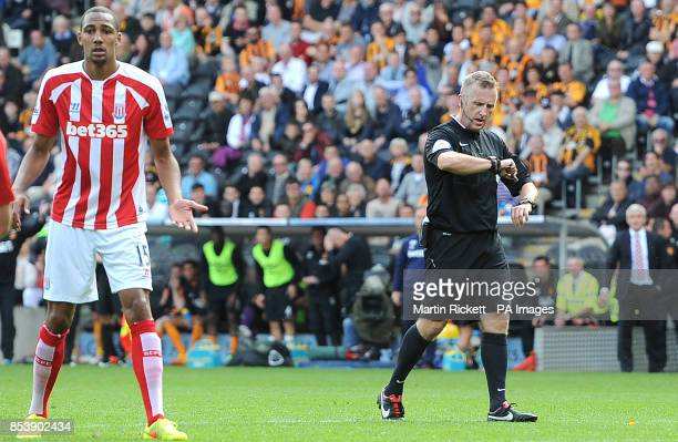 Referee Jonathan Moss checks the goal line technology on his watch before awarding a goal to Stoke City's Ryan Shawcross against Hull City during the...