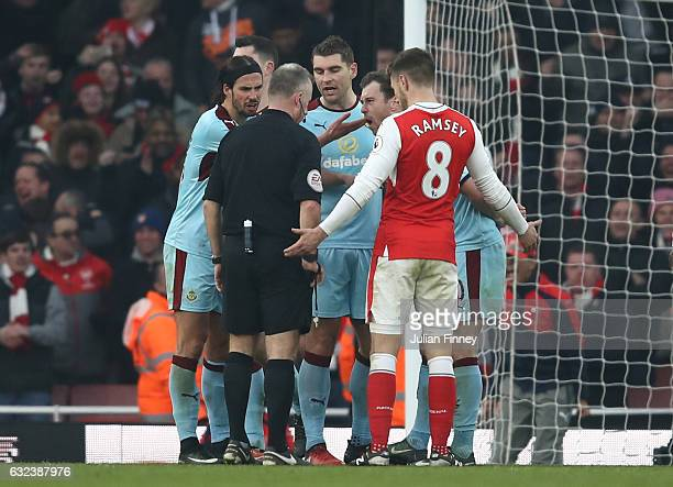 Referee Jonathan Moss is surrounded by Burnley players after awarding a penalty to Arsenal after Laurent Koscielny of Arsenal challenged by Ben Mee...