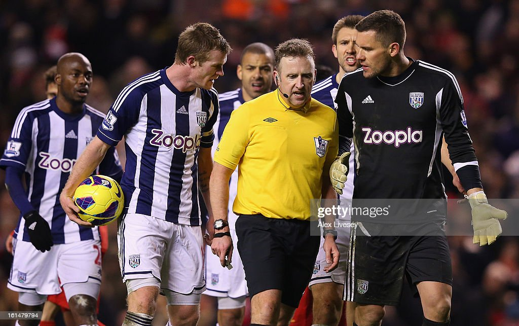 Referee Jonathan Moss is surrounded by the West Bromwich Albion players after awarding a penalty to Liverpool during the Barclays Premier League match between Liverpool and West Bromwich Albion at Anfield on February 11, 2013 in Liverpool, England.