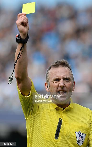 Referee Jonathan Moss issues a Yellow card during the English Premier League football match between Manchester City and Everton at The Etihad stadium...