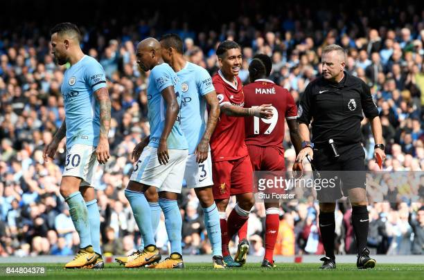 Referee Jonathan Moss looks at Ederson of Manchester City after he goes down injured during the Premier League match between Manchester City and...