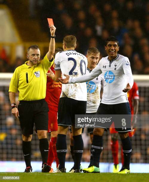 Referee Jonathan Moss shows Paulinho of Tottenham Hotspur a red card for a foul on Luis Suarez of Liverpool during the Barclays Premier League match...