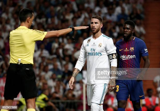 Referee Jose Sanchez Martinez warns Sergio Ramos of Real Madrid and Samuel Umtiti of Barcelona after they argued during the Spanish Super Cup return...