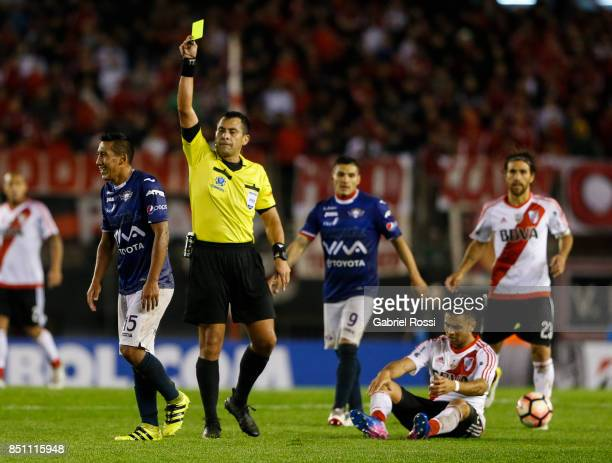 Referee Julio Bascuñán shows a yellow card to Cristhian Machado of Wilstermann during a second leg match between River Plate and Wilstermann as part...
