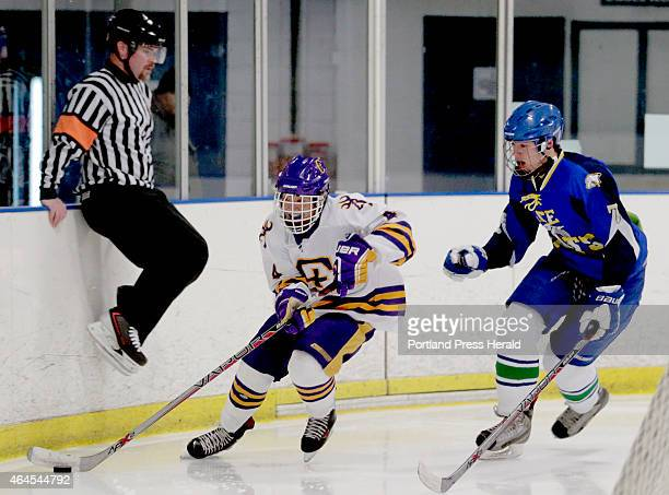 A referee jumps out of the way as Jesse CyrBrophy leads the puck past Gabe Sappington of Lake Region during a boys hockey Class A quarterfinal at...