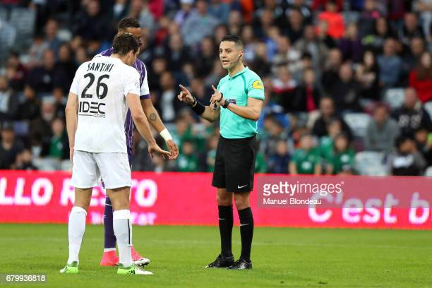 Referee Karim Abed talks to Christopher Jullien of Toulouse and Ivan Santini of Caen during the Ligue 1 match between Toulouse FC and SM Caen at...