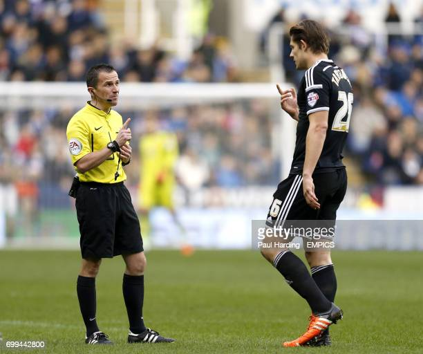 Referee Keith Stroud speaks to Brentford's James Tarkowski before showing him the yellow card