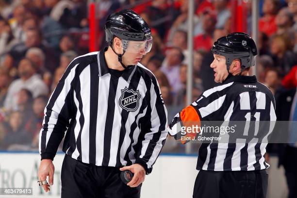 Referee Kelly Sutherland chats with NHL Linesman Scott Cherrey during a break in the action between the Florida Panthers and the Nashville Predators...