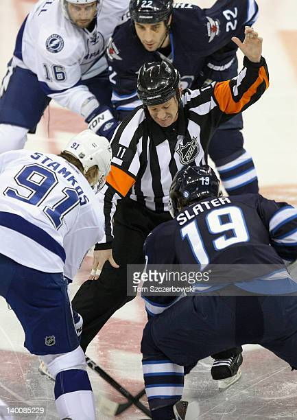 Referee Kelly Sutherland drops the puck as Steven Stamkos of the Tampa Bay Lightning faces off during their NHL game against Jim Slater of the...