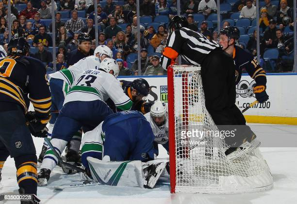 Referee Kelly Sutherland jumps onto the night to keep an eye on play between the Vancouver Canucks and Buffalo Sabres during an NHL game at the...