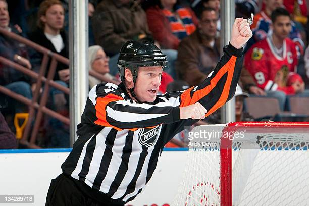 Referee Kelly Sutherland makes a high sticking call during a game between the Edmonton Oilers and the Chicago Blackhawks at Rexall Place on November...