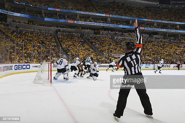 NHL referee Kelly Sutherland signals a penalty call on Ian Cole of the Pittsburgh Penguins for interference in the second period against Logan...