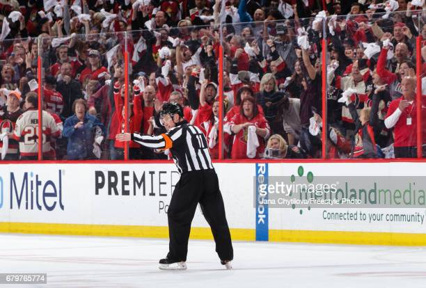 Referee Kelly Sutherland signals an overtime goal by Kyle Turris of the Ottawa Senators against the New York Rangers after a video review for an...