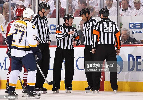 Referee Kelly Sutherland talks with linesman Jay Sharrers over a reviewed goal in Game One of the Western Conference Semifinals between the Nashville...