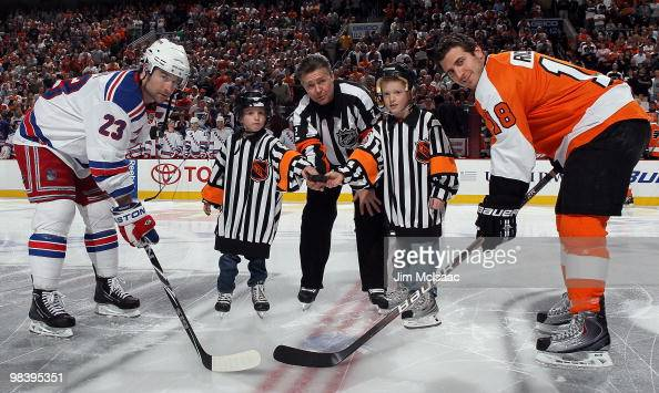 Referee Kerry Fraser is joined by his grandkids for a ceremonial puck drop between Chris Drury of the New York Rangers and Mike Richards of the...