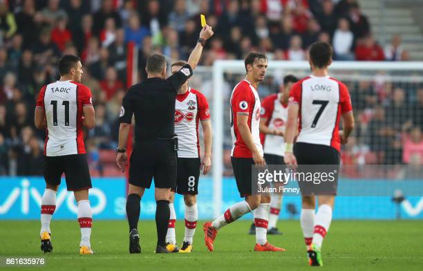 Referee Kevin Friend shows a yellow card to Manolo Gabbiadini of Southampton during the Premier League match between Southampton and Newcastle United...